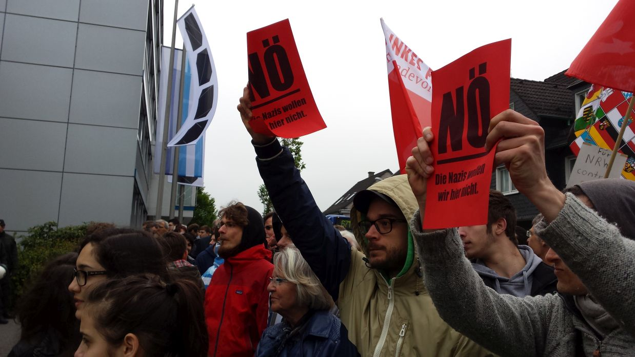 Nö - Die Nazis wollen wir hier nicht! Flugblätter des LINKEN FORUMS werden von den Gegendemonstranten hochgehalten.